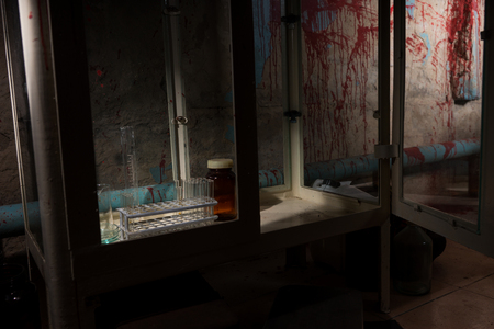grisly: Frightening Halloween theme blood of stained laboratory with glass case and test tubes holder inside