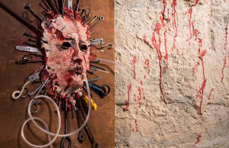 grisly: Awful bloody face stretched open on a wooden board with assorted sharp weapons alongside a blood splattered wall in a Halloween horror concept