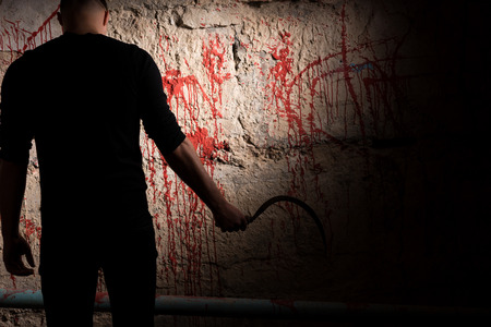 maniacal: Shadowy figure holding blade near blood stained wall for concept about murder and scary Halloween holiday