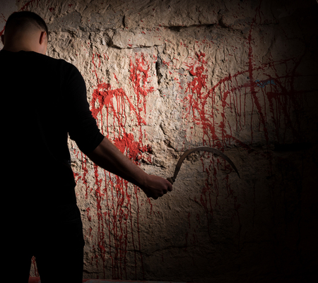 maniacal: Shadowy figure holding sickle near blood stained wall for concept about murder and scary Halloween holiday