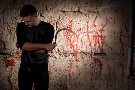 maniacal: Concentrated man holding a blade standing near blood stained wall for concept about murder and scary Halloween holiday