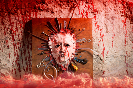 Skinned bloody face of a person stretched open on a wooden board with assorted sharp weapons alongside a blood splattered wall with red smoke below in a Halloween horror concept