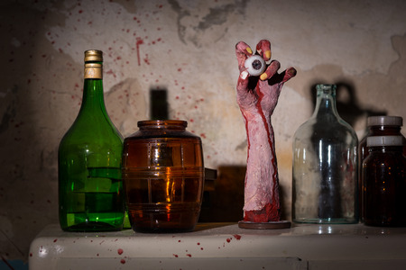 gouged: Dried up amputated hand with eyeball between glass jars with blood spattered wall Stock Photo