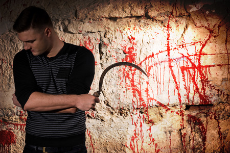 maniacal: Portrait of a man holding a blade standing near blood stained wall for concept about murder and scary Halloween holiday Stock Photo