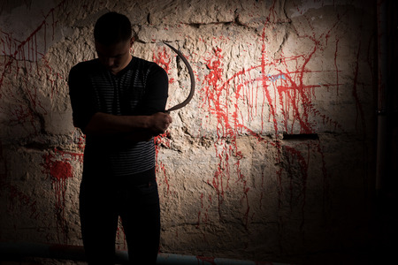 maniacal: Concentrated man holding a sickle standing near blood stained wall for concept about murder and scary Halloween holiday Stock Photo