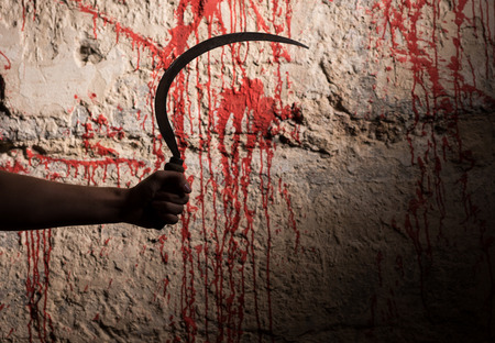 maniacal: Male hand holding a sickle in front of blood stained wall in a Halloween horror concept