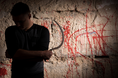 grisly: Man holding a sickle standing near blood stained wall for concept about murder and scary Halloween holiday