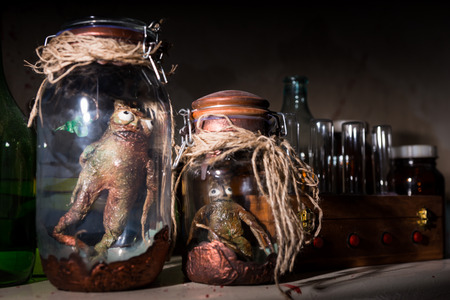 Close up of awful creatures with bulging eyes inside a pair of jars sealed with string between glass bottles with blood spattered wall in dark room in a Halloween horror concept