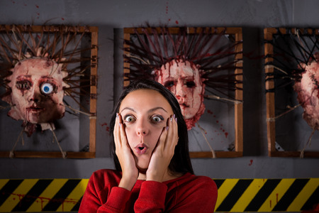 frantic: Scared girl in front of skinned faces for scary Halloween theme terror crime scene