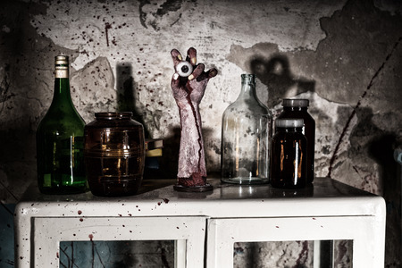 gouged: Dried up amputated hand with eyeball between glass jars with blood spattered wall in a Halloween horror concept Stock Photo