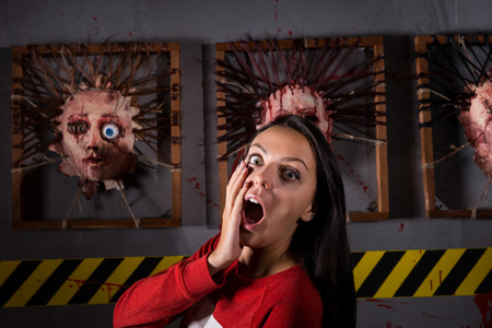 frantic: Scared attractive woman in front of skinned faces for scary Halloween theme terror crime scene Stock Photo