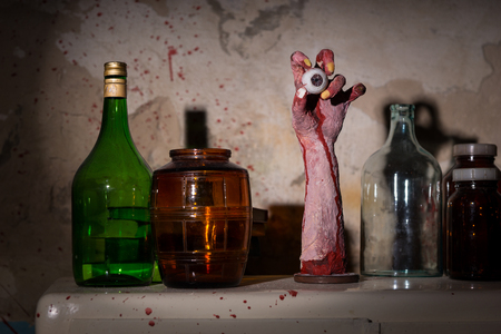 gouged: Amputated hand with eyeball between glass jars with blood spattered wall in a Halloween horror concept