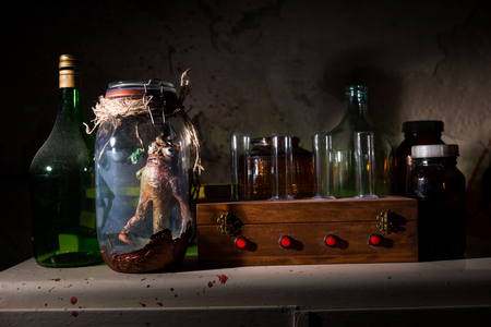 shrunken: Horrible dead creature with bulging eyes inside jar sealed with string in dark room