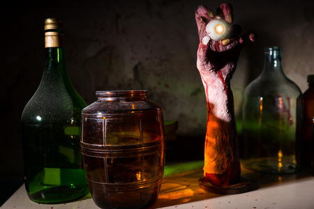 gouged: Close up of wrinkled hand with eyeball between glass jars with blood spattered wall in a Halloween horror concept