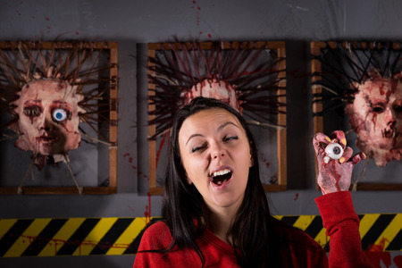 depraved: Single young strange woman yawns while holding eyeball in wrinkled hand for concept about Halloween or torture