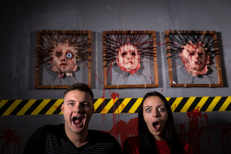 ghoulish: Scared couple in front of skinned faces for scary Halloween theme terror crime scene