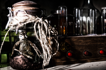 Awful creature with bulging eyes inside jar sealed with string between glass jars and bottles with blood spattered wall in dark room in a Halloween horror concept Stock Photo