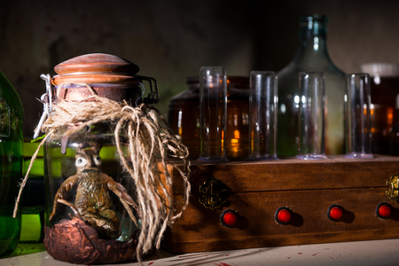 grisly: Dead creature with bulging eyes inside jar sealed with string between glass jars and bottles with blood spattered wall in dark room in a Halloween horror concept