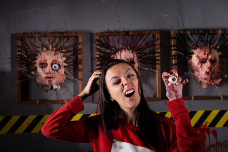 woman eyeball: Single young strange woman scratching head while holding eyeball in wrinkled hand for concept about Halloween or torture