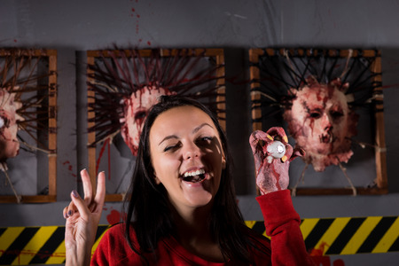 depraved: Young strange woman showing peace and holding eyeball in wrinkled hand for concept about Halloween or torture