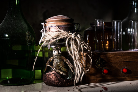 ghoulish: Horrible dead creature with bulging eyes inside jar sealed with string between glass jars and bottles with blood spattered wall in dark room in a Halloween horror concept
