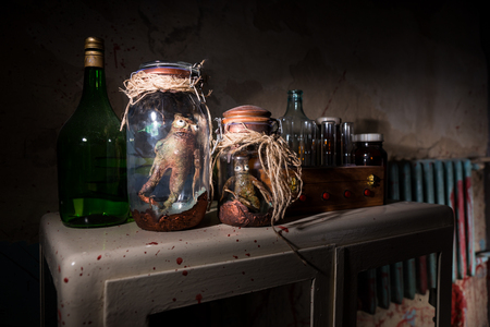 Horrible dead creatures with bulging eyes inside a pair of mason jars sealed with string in dark room in a Halloween horror concept