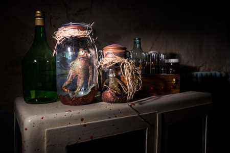 Horrible dead creatures with bulging eyes inside a pair of mason jars sealed with string in dark room