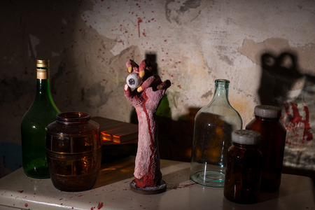 gouged: Wrinkled hand with eyeball between glass jars with blood spattered wall in a Halloween horror concept