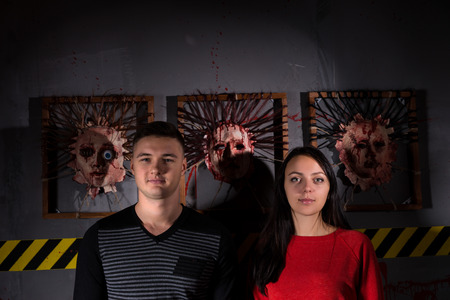 gory: Young man and woman in front of skinned faces for scary Halloween theme terror crime scene