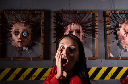 frantic: Scared young woman in front of skinned faces for scary Halloween theme terror crime scene