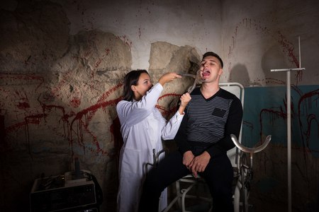 maniacal: Female scientist holding medical forceps in front of patient and tries to cut off the tongue in dungeon with bloody walls in a Halloween horror concept
