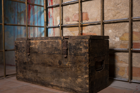 gory: Old chest in the iron cage behind blood splattered wall for concept about scary Halloween theme