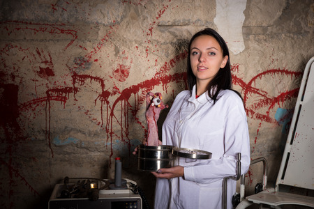 psychotic: Female crazy scientist holding a severed hand and eyeball in a box in front of a blood splattered wall, Halloween concept Stock Photo