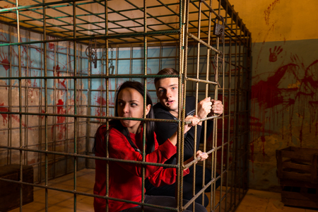 imprisoned: Couple of Halloween victims imprisoned in a metal cage with a blood splattered wall behind them looking out through the bars