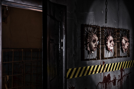 frightful: Frightful open iron door near ghastly faces stuck in square frames above yellow and black warning symbol and bloody wall in basement in a Halloween horror concept Stock Photo