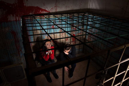 gory: Two frightened Halloween victims imprisoned in a metal cage with a blood splattered wall behind them sitting in terror awaiting their fate