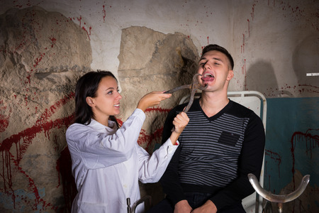 maniacal: Female crazy scientist holding medical forceps in front of patient and tries to cut off the tongue in dungeon with bloody walls in a Halloween horror concept