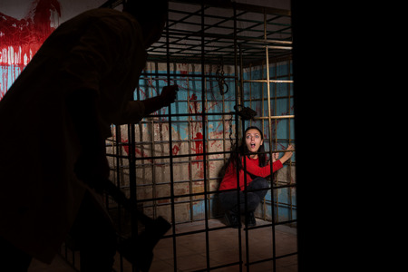 grisly: Shadowy male figure holding an ax in front of frightened female victim imprisoned in a metal cage with a blood splattered wall behind her sitting in terror awaiting a fate