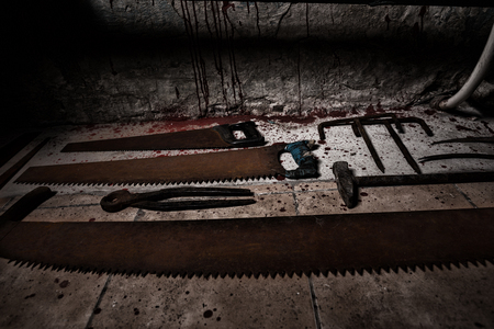 maniacal: Saws, sickles and other devices on the bloody floor  in basement with pipes and wires in a Halloween horror concept