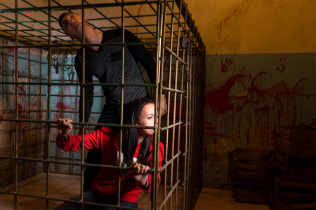 imprisoned: Couple afraid Halloween victims imprisoned in a metal cage with a blood splattered wall behind them looking out through the bars