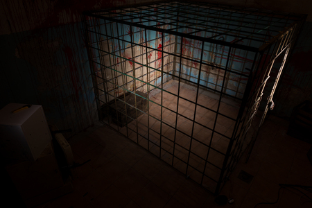grisly: Empty iron cage in basement with blood splattered wall for concept about scary Halloween theme