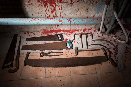 maniacal: Saws, tongs and other devices on the bloody floor  in basement with pipes and wires in a Halloween horror concept