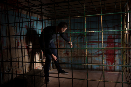 ghoulish: Young man imprisoned in a metal cage with a blood splattered wall behind him shackled for concept about torture or scary Halloween theme Stock Photo