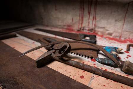 maniacal: Close up of saws, sickles, hammer and other devices on the bloody floor in basement in a Halloween horror concept Stock Photo