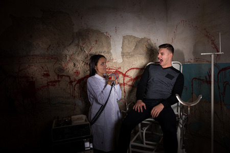 maniacal: Demented scientist holding electrical shocking devices in front of patient in dungeon with bloody walls in a Halloween horror concept