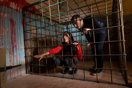imprisoned: Two victims imprisoned in a metal cage with a blood splattered wall behind them, girl pulling her hand through the bars and trying to get out