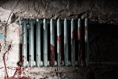 maniacal: Terrible bloodied battery in dimly lit basement in a Halloween horror concept