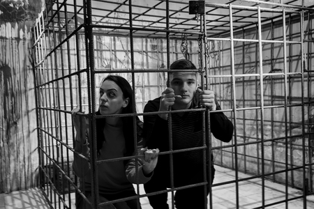 grisly: Black and white picture of couple afraid Halloween victims imprisoned in a metal cage with a blood splattered wall behind them looking out through the bars