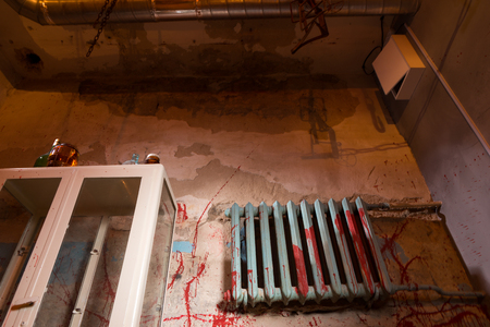 maniacal: Terrible bloodied battery near glass case in dimly lit basement with pipes and wires in foreground in a Halloween horror concept Stock Photo