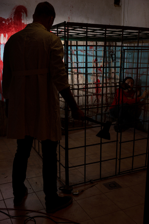 imprisoned: Shadowy male figure holding an ax in front of scared victim imprisoned in a metal cage with a blood splattered wall behind her sitting in terror awaiting a fate